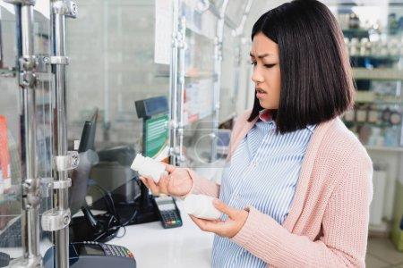 Photo pour Mécontent asiatique femme tenant bouteilles avec pilules dans drugstore - image libre de droit