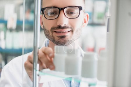 Photo for Cheerful pharmacist in eyeglasses taking bottle with pills from glass shelf on blurred foreground - Royalty Free Image