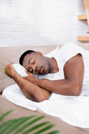 Photo for African american man in white t-shirt sleeping on bed at home - Royalty Free Image