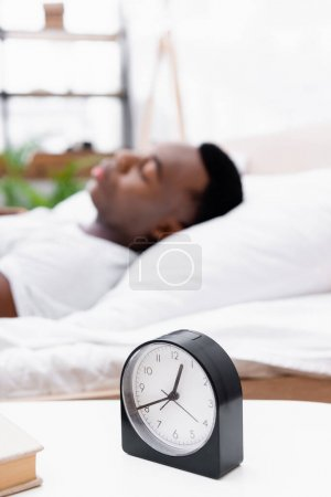 Clock and book on bedside table near african american man sleeping on blurred background