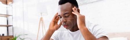 Hombre afroamericano que sufre de dolor de cabeza en el dormitorio, pancarta