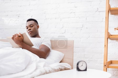 African american man reading book near clock on bedside table on blurred foreground