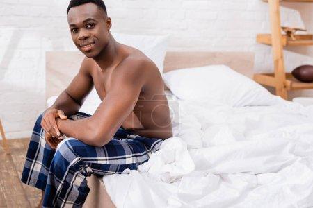 Photo pour Sans chemise homme afro-américain assis sur le lit et souriant à la caméra - image libre de droit