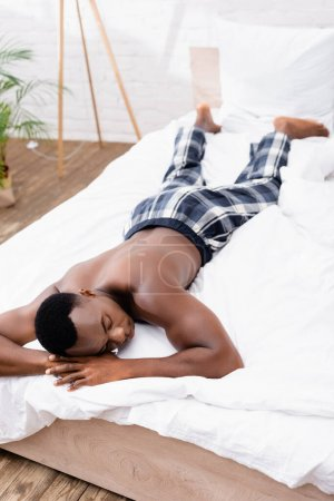 Shirtless african american man sleeping on bed at morning