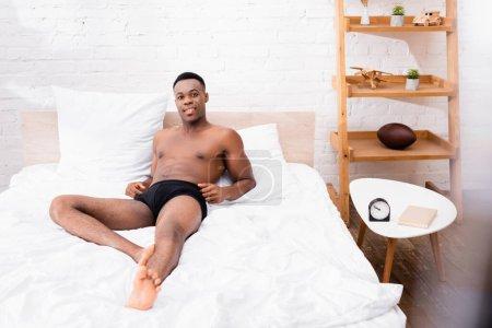 Photo pour Afro-américain en sous-vêtements regardant la caméra sur le lit - image libre de droit