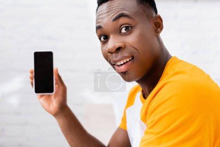 Photo pour Souriant homme afro-américain regardant la caméra tout en tenant smartphone avec écran blanc sur fond flou - image libre de droit