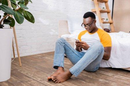 Photo pour Homme afro-américain pieds nus dans les lunettes en utilisant un smartphone sur le sol dans la chambre - image libre de droit