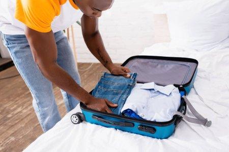 Photo pour Afro-Américain homme mettre jeans près de chemise dans la valise avant les vacances - image libre de droit