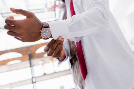 Cropped view of wristwatch on arm of african american businessman wearing white shirt on blurred background