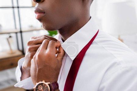 Photo pour Vue recadrée de l'homme d'affaires afro-américain boutonnage chemise à la maison - image libre de droit