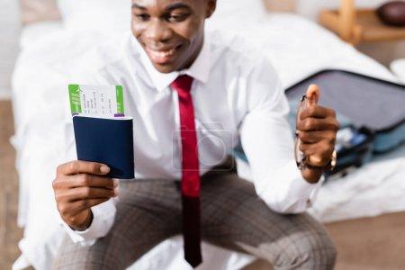 Photo pour Passeport avec billet d'avion et lunettes dans les mains d'un homme d'affaires afro-américain sur fond flou - image libre de droit