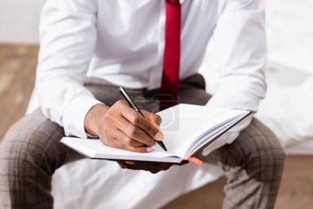 Photo pour Vue recadrée d'un homme d'affaires afro-américain écrivant sur un carnet sur un fond flou au lit - image libre de droit