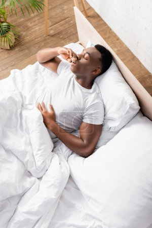 High angle view of african american man sleeping on bed at morning