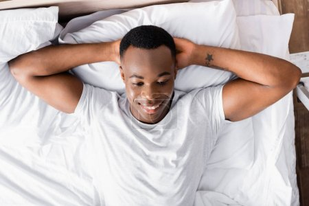 Photo for Top view of smiling african american man lying on bed - Royalty Free Image