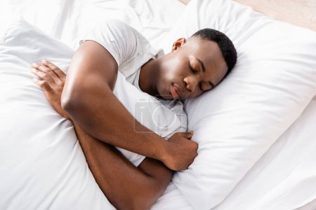 Photo for High angle view of african american man embracing pillow while sleeping at home - Royalty Free Image