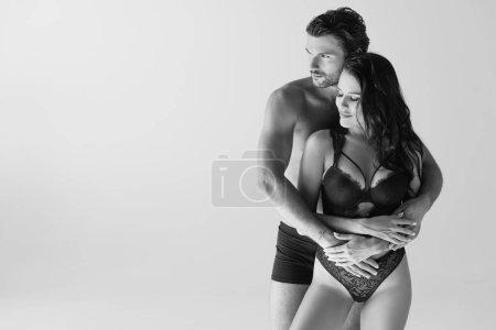 Photo pour Plan monochrome d'un homme en caleçon embrassant une femme souriante en lingerie isolée sur gris - image libre de droit