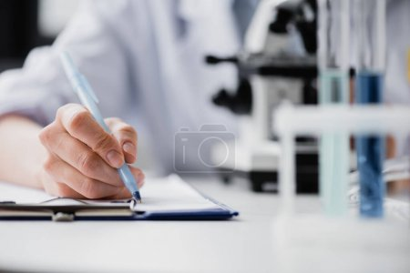 partial view of nurse writing on clipboard near microscope on blurred background