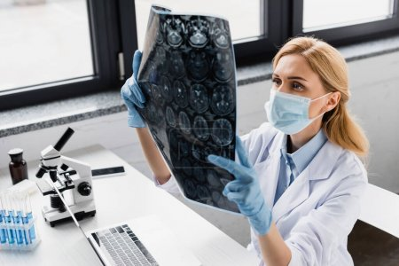 Photo for Scientist in medical mask looking at x-ray near devices and microscope on desk - Royalty Free Image