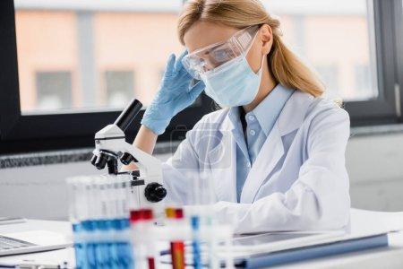 Müder Wissenschaftler in medizinischer Maske und Brille mit Migräne im Labor