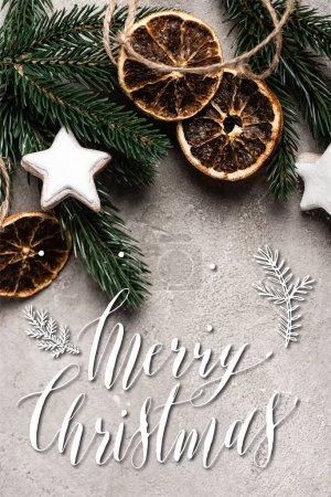 Photo for Top view of dried orange slices, cookies and pine branch near merry christmas lettering on textured background - Royalty Free Image