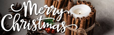 decorated candles with cinnamon sticks near pine cones and merry christmas lettering, banner
