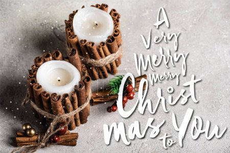 Scented candles decorated with cinnamon sticks near a very merry christmas to you lettering on textured grey background