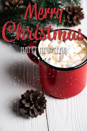 red cup of cocoa near pine cone and merry christmas, happy new year lettering on blurred wooden background