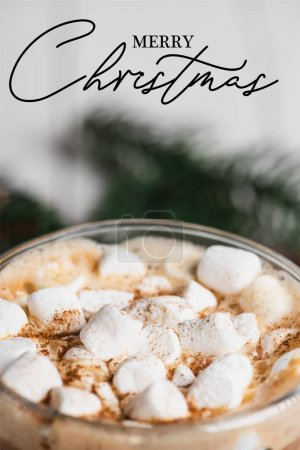 Photo for Close up view of glass cup of cocoa with marshmallows and cinnamon near merry christmas lettering - Royalty Free Image