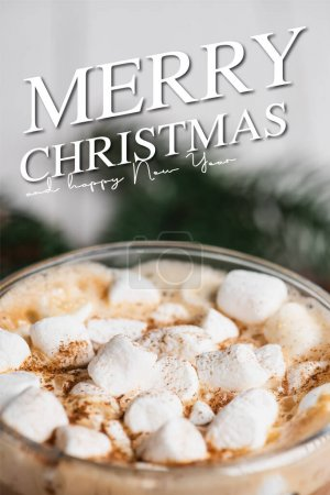Close up view of glass cup of cocoa with marshmallows and cinnamon near merry christmas and happy new year lettering