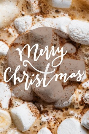 Close up view of cocoa, marshmallows and cinnamon with merry christmas lettering