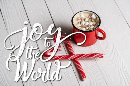 Red cup of cocoa near christmas candy canes near joy to the world lettering on wooden background