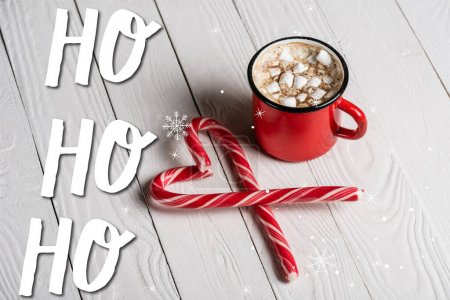 Photo for Red cup of cocoa near christmas candy canes near  ho ho ho lettering on wooden background - Royalty Free Image