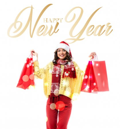 pleased woman in santa hat and scarf with ornament holding red shopping bags near happy new year lettering on white