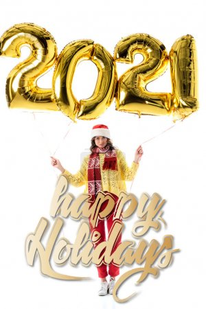 Photo for Young woman in santa hat and scarf holding balloons with 2021 numbers near happy holidays lettering on white - Royalty Free Image