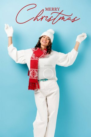 Photo for Joyful woman in winter outfit, warm scarf, gloves and hat standing with outstretched hands near merry christmas lettering on blue - Royalty Free Image