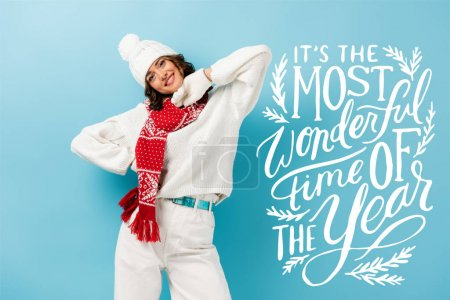 Photo for Pleased young woman in white winter outfit, warm scarf, gloves and hat standing near its the most wonderful time of the year lettering on blue - Royalty Free Image