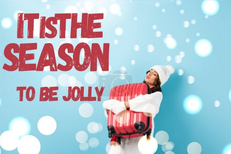 Photo for Young woman in winter outfit carrying heavy suitcase near it is the season to be jolly lettering on blue - Royalty Free Image