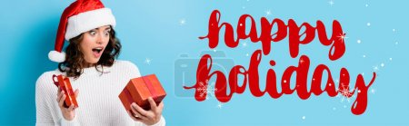 Photo for Young shocked woman looking at gift box near happy holidays lettering on blue, banner - Royalty Free Image