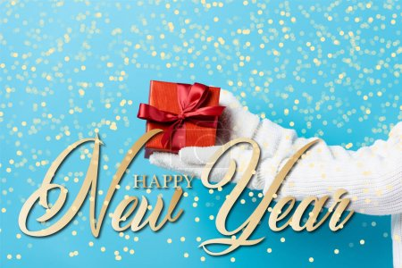 Photo for Cropped view of young woman in gloves holding gift box near happy new year lettering on blue - Royalty Free Image