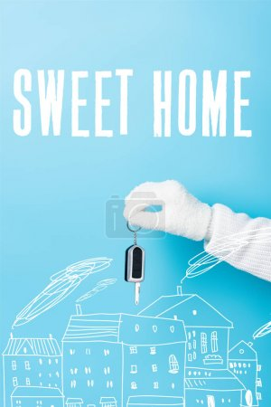cropped view of woman in white glove holding key near sweet home lettering and houses illustration on blue
