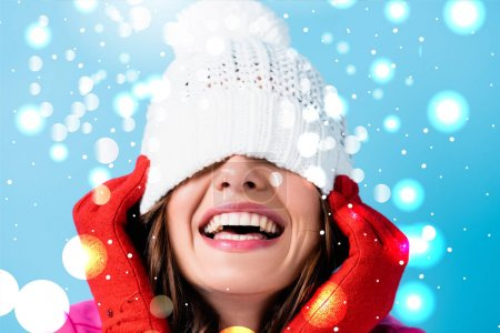 joyful woman in red gloves covering eyes while adjusting white hat near snow illustration on blue