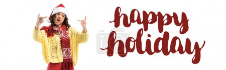 Photo for Young woman in santa hat and scarf showing middle fingers near happy holidays lettering on white, banner - Royalty Free Image
