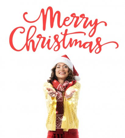 joyful young woman in santa hat and scarf standing with outstretched hands near merry christmas lettering on white