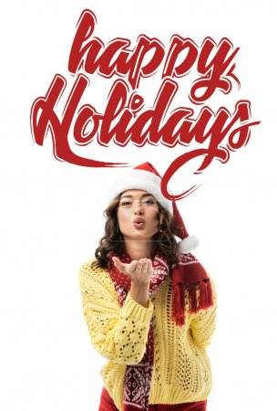 Photo for Young woman in santa hat and scarf sending air kiss near happy holidays lettering on white - Royalty Free Image