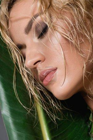 Photo pour Femme blonde aux cheveux mouillés, les yeux fermés et la feuille verte - image libre de droit