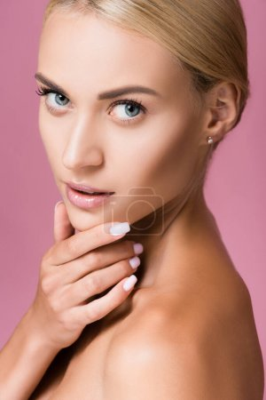 Photo for Beautiful blonde woman with perfect skin touching face isolated on pink - Royalty Free Image