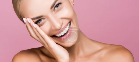 Photo for Smiling beautiful blonde woman touching face isolated on pink, banner - Royalty Free Image