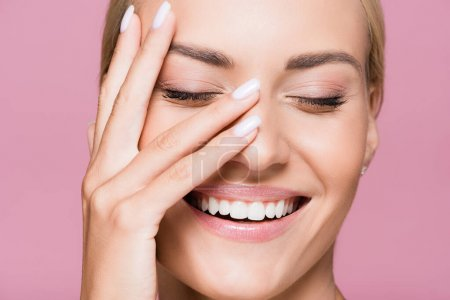lächelnd schöne blonde Frau posiert mit der Hand auf dem Gesicht isoliert auf rosa