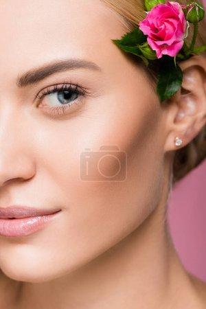 primer plano de hermosa mujer rubia con la piel perfecta y flor de rosa en el pelo aislado en rosa