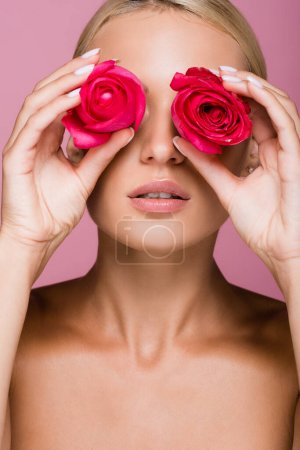 beautiful blonde woman with rose flowers on eyes isolated on pink